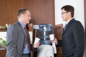 Businessmen talking at water cooler